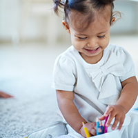Young smiling child playing with colorful pencils.
