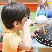 Elementary-age child looking at a planet through a magnifying glass in a classroom.