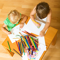 Children drawing on paper with colored pencils in a learning center.